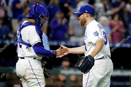 Kansas City Royals relief pitcher Ian Kennedy and catcher Meibrys Viloria celebrate after the team's baseball game against the Detroit Tigers, in Kansas City, Mo. The Royals won 5-4