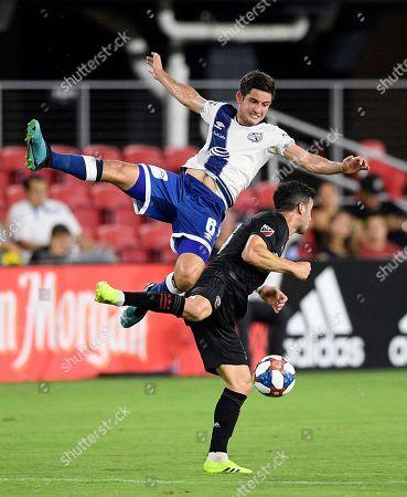 Puebla midfielder Daniel Lajud (6) goes airborne over D.C. United midfielder Felipe Martins during the first half of a friendly soccer match, in Washington