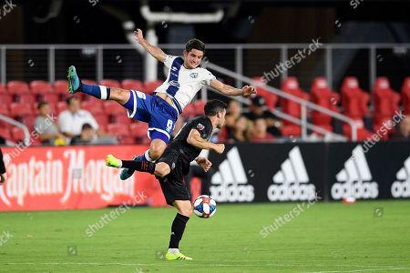 Puebla midfielder Daniel Lajud (6) goes airborne against D.C. United midfielder Felipe Martins, right, during the first half of an international friendly soccer match, in Washington