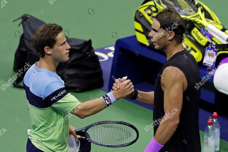 Diego Schwartzman, left, of Argentina, clasps hands with Rafael Nadal, of Spain, after Nadal defeated Schwartzman during the quarterfinals of the U.S. Open tennis tournament early, in New York
