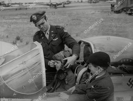 WWII: America: Air Force: In England: To mark the 38th anniversary of the formation of the U.S. Army Air Force, the first and last to operate from Britain, today threw open fifteen airfields to the public. This picture taken at Bury St. Edmunds, shows Lt. Guy Clark of Antrim, New Hampshire, lets a schoolboy guest try on his pilot's helmet and mask