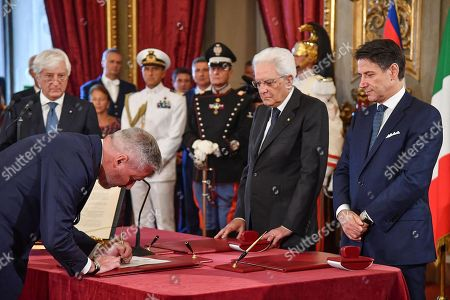 Italian Minister of Defence (L) Lorenzo Guerini signs in front of Italian Premier Giuseppe Conte (R) and President Sergio Mattarella (2-R) during the new government's swearing-in at Quirinal Palace, Rome, Italy, 05 September 2019. Italian Prime Minister Giuseppe Conte's new government is a coalition between the anti-establishment 5-Star Movement (M5S) and the center-left Democratic Party (PD) that will have 21 ministers, 10 from the M5S, nine from the PD and one from the small leftwing Free and Equal (LeU) party, media reported.