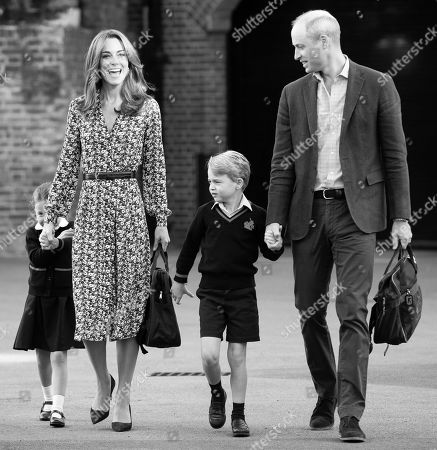 Princess Charlotte hides behind her mother Catherine Duchess of Cambridge as she arrives for her first day of school at Thomas's Battersea in London, accompanied by her brother Prince George and her father Prince William.
