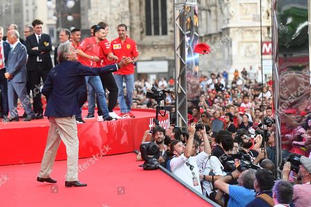 Former Ferrari chairman Luca Cordero Di Montezemolo throws hats into the crowd during the celebration of the 90th anniversary of Ferrari Foundation in Cathedral square in Milan