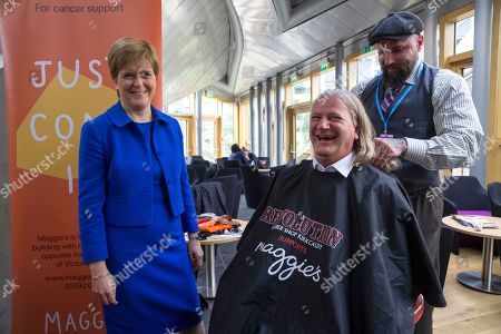 Chop the Mop photocall at The Scottish Parliament in support of the Maggie's Fife cancer support centre - Nicola Sturgeon, First Minister of Scotland and Leader of the Scottish National Party (SNP), waits while Mark Reynolds, owner of Kirkcaldy business Revolution Barbershop, prepares the hair of David Torrance, SNP MSP for Kirkcaldy, who has been growing his hair for the past year.