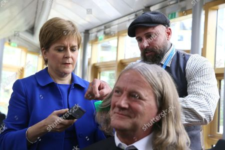 Chop the Mop photocall at The Scottish Parliament in support of the Maggie's Fife cancer support centre - Nicola Sturgeon, First Minister of Scotland and Leader of the Scottish National Party (SNP) is guided by Mark Reynolds, owner of Kirkcaldy business Revolution Barbershop, before she cuts the hair of David Torrance, SNP MSP for Kirkcaldy, who has been growing his hair for the past year.