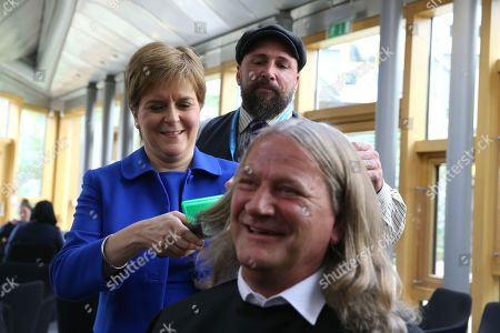 Chop the Mop photocall at The Scottish Parliament in support of the Maggie's Fife cancer support centre - Nicola Sturgeon, First Minister of Scotland and Leader of the Scottish National Party (SNP) is guided by Mark Reynolds, owner of Kirkcaldy business Revolution Barbershop, while she cuts the hair of David Torrance, SNP MSP for Kirkcaldy, who has been growing his hair for the past year.