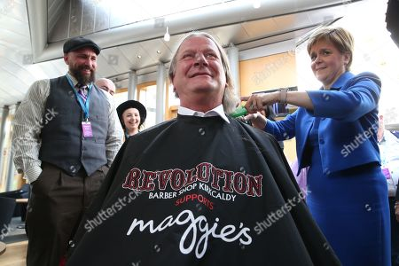 Stock Photo of Chop the Mop photocall at The Scottish Parliament in support of the Maggie's Fife cancer support centre - Nicola Sturgeon, First Minister of Scotland and Leader of the Scottish National Party (SNP) is guided by Mark Reynolds, owner of Kirkcaldy business Revolution Barbershop, while she cuts the hair of David Torrance, SNP MSP for Kirkcaldy, who has been growing his hair for the past year.