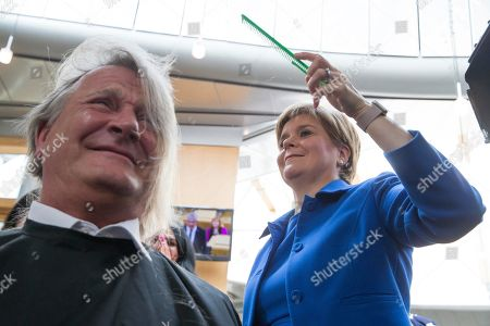 Chop the Mop photocall at The Scottish Parliament in support of the Maggie's Fife cancer support centre - Nicola Sturgeon, First Minister of Scotland and Leader of the Scottish National Party (SNP), cuts the hair of David Torrance, SNP MSP for Kirkcaldy, who has been growing his hair for the past year.