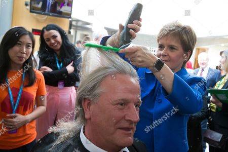 Stock Image of Chop the Mop photocall at The Scottish Parliament in support of the Maggie's Fife cancer support centre - Nicola Sturgeon, First Minister of Scotland and Leader of the Scottish National Party (SNP), cuts the hair of David Torrance, SNP MSP for Kirkcaldy, who has been growing his hair for the past year.