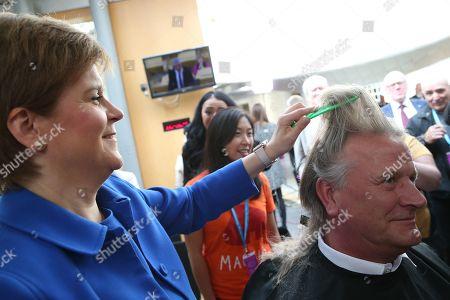 Editorial photo of Nicola Sturgeon, First Minister of Scotland, cutting the hair of David Torrance MSP, The Scottish Parliament, Edinburgh, Scotland, UK - 05 September 2019