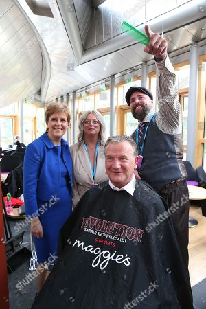 Stock Picture of Chop the Mop photocall at The Scottish Parliament in support of the Maggie's Fife cancer support centre - Nicola Sturgeon, First Minister of Scotland and Leader of the Scottish National Party (SNP), Sylvia Wood, David Torrance, SNP MSP for Kirkcaldy, who has been growing his hair for the past year, and Mark Reynolds, who owns Kirkcaldy business Revolution Barbershop.