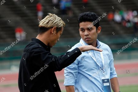 Keisuke Honda, left, of Japan gestures before the World Cup Group C qualifying soccer match between Cambodia and Hong Kong in Phnom Penh, Cambodia