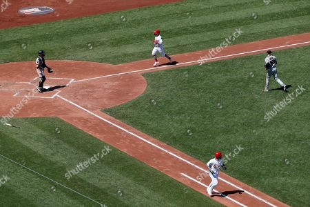 St. Louis Cardinals' Yadier Molina, bottom heads to first for a single as teammate Kolten Wong, top, comes in to score between San Francisco Giants catcher Stephen Vogt, left, and starting pitcher Logan Webb, right, during the third inning of a baseball game, in St. Louis