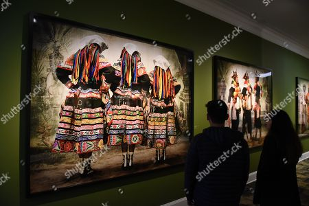 People look at the paintings during the exhibition in Lima