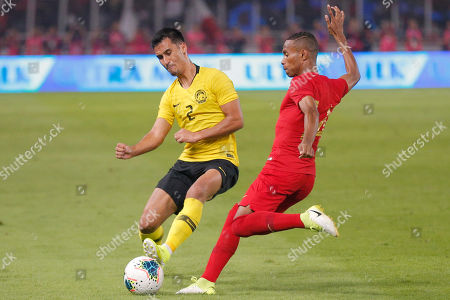 Indonesia's Ruben Sanadi, right, fights for the ball with Malaysia's Matthew Davies during their World Cup Group G Asia qualifying match between Indonesia and Malaysia at Gelora Bung Karno Stadium in Jakarta, Indonesia