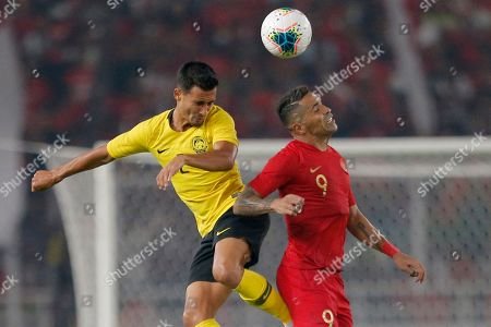 Indonesia's Alberto Goncalves, right, fights for the ball with Malaysia's Matthew Davies during their World Cup Group G Asia qualifying match between Indonesia and Malaysia at Gelora Bung Karno Stadium in Jakarta, Indonesia