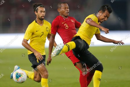 Indonesia's Yustinus Paew, center, fights for the ball with Malaysia's Corbin Ong Lawrence, left, and Adam Nor Azlin during their World Cup Group G Asia qualifying match between Indonesia and Malaysia at Gelora Bung Karno Stadium in Jakarta, Indonesia
