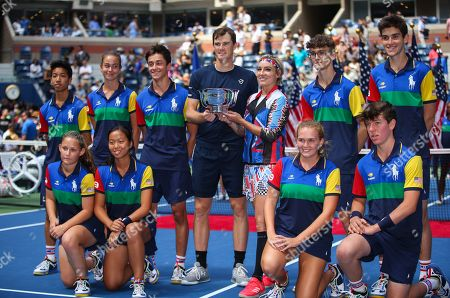 Jamie Murray of Great Britain and Bethanie Mattek-Sands of USA pose alongside the ball boys and ball girls with the Mixed Doubles trophy
