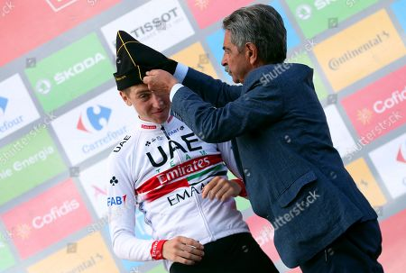 Slovenian rider Tadej Pogacar (L) of the UAE Team Emirates receives a traditional hat from Cantabria's regional president Miguel Angel Revilla (R) on the podium after winning the 13th stage of the Vuelta a Espana cycling race over 166.4km from Bilbao to Los Machucos, northern Spain, 06 September 2019.