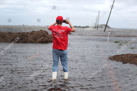 Mike Rogers takes a photo of the storm surge from Hurricane Dorian that blocks Cedar Island off from the mainland on NC 12 in Atlantic, N.C., after Hurricane Dorian past the coast on