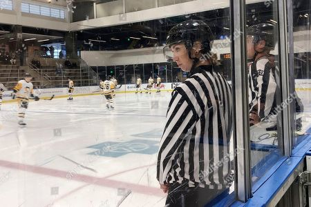 Stock Photo of Linesman Kirsten Welsh watches at center ice as Pittsburgh Penguins and Boston Bruins players take the ice to prepare to play in the Sabres prospects hockey tournament, in Buffalo, N.Y. Welsh is one four female officials selected to be the first women to work as on-ice officials at several prospect tournaments taking place across the country this weekend. The other three other women selected were Katie Guay, Kelly Cooke and Kendall Hanley