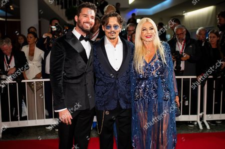 Monika Bacardi, Johnny Depp, Andrea Iervolino. Andrea Iervolino, from left, Johnny Depp and Monika Bacardi pose for photographers upon arrival at the premiere of the film 'Waiting for the Barbarians' at the 76th edition of the Venice Film Festival, Venice, Italy