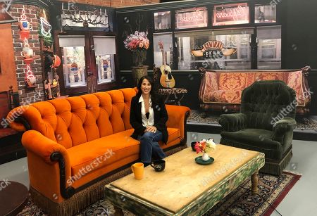 """This photo shows actress Maggie Wheeler, who played Janice on the NBC sitcom """"Friends,"""" posing in a replica of the Central Perk set, at the New York City Pop-Up experience in New York. There are different sections to walk through in 8,500 square feet of loft space, where more than 50 original props from the show are on display. The popular comedy is celebrating its 25th anniversary this year"""