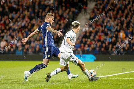 Liam Cooper (Leeds United) stretches to stop the cross from Aleksandr Golovin (Monaco) during the UEFA European 2020 Qualifier match between Scotland and Russia at Hampden Park, Glasgow