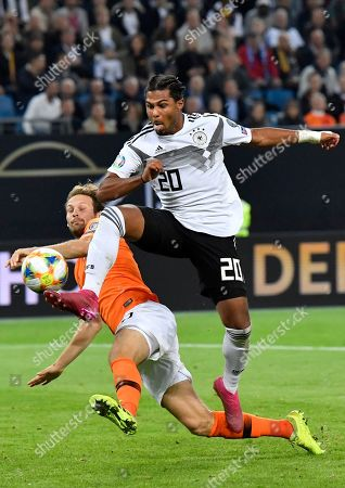 Germany's Serge Gnabry vies for the ball with Netherlands' Daley Blind, left, during the Euro 2020 group C qualifying soccer match between Germany and the Netherlands at the Volksparkstadion in Hamburg, Germany