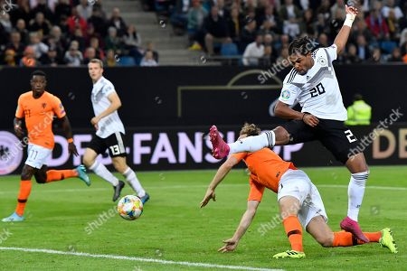 Germany's Serge Gnabry vies for the ball with Netherlands' Daley Blind, 2nd right, during the Euro 2020 group C qualifying soccer match between Germany and the Netherlands at the Volksparkstadion in Hamburg, Germany
