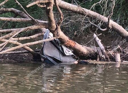 This photo provided by Louisiana Department of Wildlife and Fisheries Enforcement Division shows motorboat that crashed into a fallen tree on in Upper Amite River north of Bayou Manchac, La. The Department of Wildlife and Fisheries says a 23-year-old woman was injured in the wreck that killed 29-year-old Dustin Gore of St. Amant and 27-year-old Trent Kelly of Baton Rouge. Agents found the men's bodies near the 16-foot aluminum boat