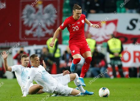 Poland's Piotr Zielinski, right, fights for the ball with the Slovenia's Roman Bezjak, left, and Slovenia's Josip Ilicic during the Euro 2020 group G qualifying soccer match between Slovenia and Poland at Stozice stadium in Ljubljana, Slovenia