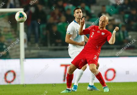 Slovenia's Andraz Sporar, left, fights for the ball with the Poland's Michal Pazdan, right, during the Euro 2020 group G qualifying soccer match between Slovenia and Poland at Stozice stadium in Ljubljana, Slovenia