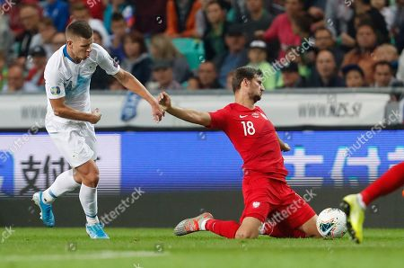 Slovenia's Roman Bezjak, left, fights for the ball with the Poland's Bartosz Bereszynski, right, during the Euro 2020 group G qualifying soccer match between Slovenia and Poland at Stozice stadium in Ljubljana, Slovenia