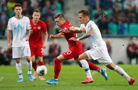 Poland's Piotr Zielinski, second right, fights for the ball with the Slovenia's Jure Balkovec, right, during the Euro 2020 group G qualifying soccer match between Slovenia and Poland at Stozice stadium in Ljubljana, Slovenia
