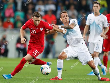 Poland's Piotr Zielinski, left, fights for the ball with the Slovenia's Jure Balkovec, right, during the Euro 2020 group G qualifying soccer match between Slovenia and Poland at Stozice stadium in Ljubljana, Slovenia