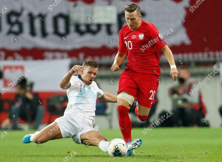Slovenia's Roman Bezjak, left, fights for the ball with the Poland's Piotr Zielinski, right, during the Euro 2020 group G qualifying soccer match between Slovenia and Poland at Stozice stadium in Ljubljana, Slovenia