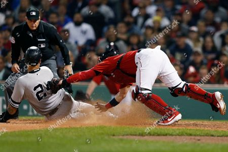 Boston Red Sox's Christian Vazquez, right, tags New York Yankees' Gary Sanchez (24) trying to score on a single by Brett Gardner during the seventh inning of a baseball game in Boston