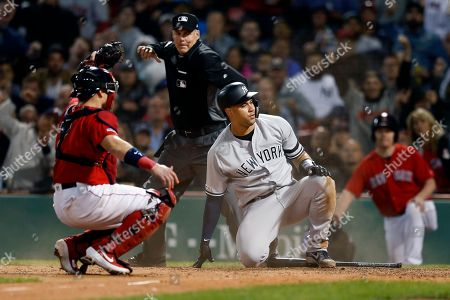 Boston Red Sox's Christian Vazquez, left, holds the ball as New York Yankees' Gary Sanchez is called out trying to score on a single by Brett Gardner during the seventh inning of a baseball game in Boston