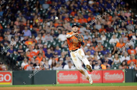 Houston Astros shortstop Alex Bregman throws to first for the out after fielding a ground ball by Seattle Mariners' Tom Murphy during the fifth inning of a baseball game, in Houston