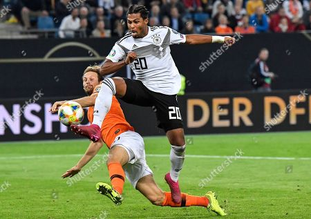 Germany's Serge Gnabry, right, and Netherland's Netherland's Daley Blind challenge for the ball during the Euro 2020 group C qualifying soccer match between Germany and The Netherlands in Hamburg, Germany