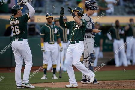 Chad Pinder, Matt Chapman. Oakland Athletics' Chad Pinder, right, celebrates with Matt Chapman (26) after hitting a two-run home run off Detroit Tigers' David McKay in the ninth inning of a baseball game that was suspended due to rain earlier in the season, in Oakland, Calif