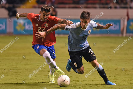 Costa Rica's Ronald Matarrita, left, and Uruguay's Brian Rodriguez fight for the ball during a friendly soccer match at the National Stadium in San Jose, Costa Rica