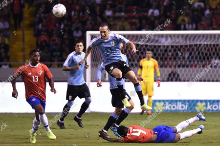 Uruguay's Diego Laxalt (17) jumps over Keysher Fuller, bottom, during a friendly soccer match at the National Stadium in San Jose, Costa Rica