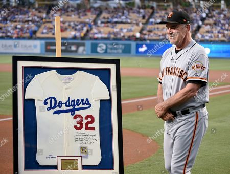 Stock Image of San Francisco Giants manager Bruce Bochy smiles after receiving a signed Sandy Koufax jersey to commemorate his last series at Dodger Stadium as Giants manager, prior to the team's baseball game against the Los Angeles Dodgers in Los Angeles