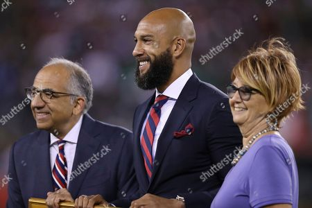 United States Soccer Federation President Carlos Cordeiro, left, honors former United States goalkeeper Tim Howard, center, before an international friendly soccer match between the United States and Mexico, in East Rutherford, N.J. Mexico won 3-0