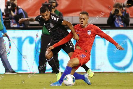 Mexico forward Jesus Manuel Corona, left, and United States defender Sergiño Dest battle for the ball during an international friendly soccer match, in East Rutherford, N.J. Mexico won 3-0