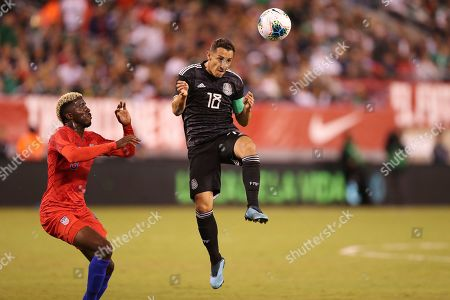 Mexico midfielder Andres Guardado, center, jumps up the head the ball while United States forward Gyasi Zardes attempts to defend during an international friendly soccer match, in East Rutherford, N.J. Mexico won 3-0