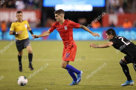 United States midfielder Christian Pulisic, left, moves the ball away from Mexico defender Jorge Sanchez during an international friendly soccer match, in East Rutherford, N.J. Mexico won 3-0